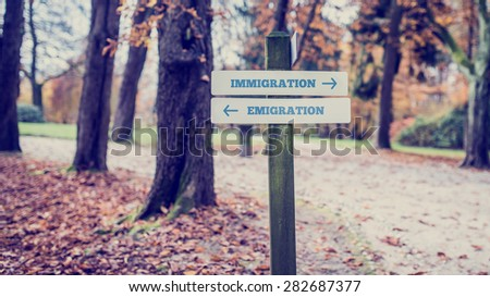 Old Wooden Signpost at the Peaceful Park with Conceptual Directions for Immigration and Emigration. - stock photo
