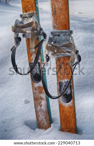 old wooden skis in the snow, vertical - stock photo