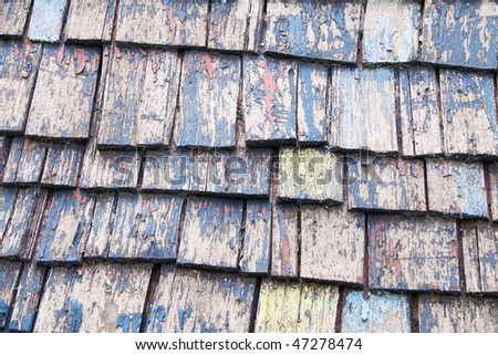 old wooden slated roof top with peeling paint and cracks in the wood - stock photo
