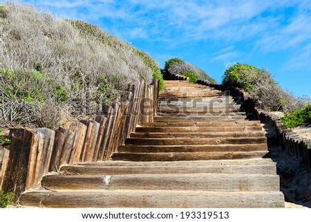 Old wooden stairways to the see beach, but it looks like a stairways to sky or stairways to haven - stock photo