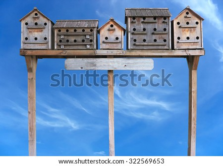 Old wooden starling nesting boxes bird house over blue sky background - stock photo