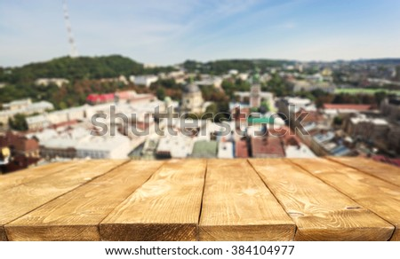 Old wooden table and cityscape on background - stock photo