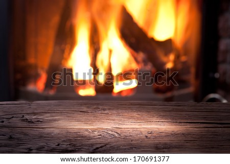 Old wooden table in front of the fireplace. - stock photo