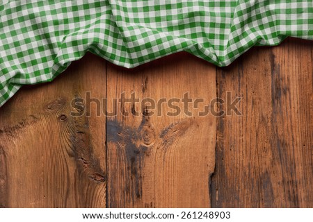 old wooden table with picnic tablecloth and copyspace - stock photo