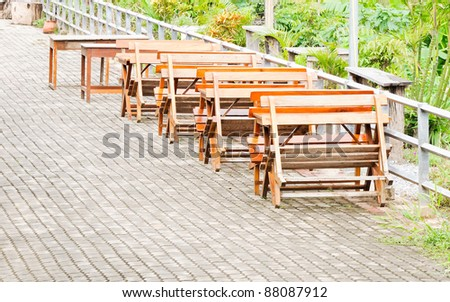 Old wooden tables and bench for seating on the walkway behind the house - stock photo