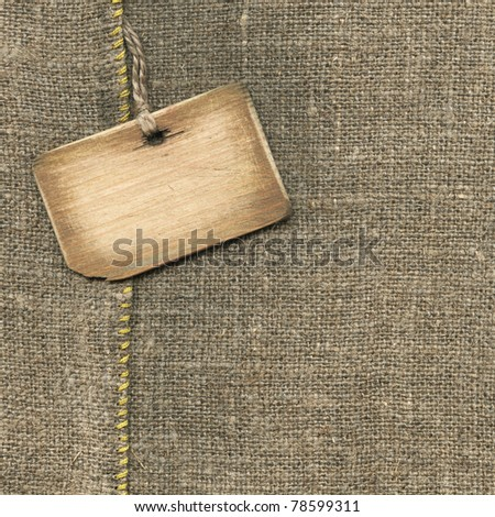 Old wooden tag on the sacking - stock photo