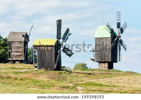 Old wooden traditional ukrainian windmill over blue sky with clouds - stock photo