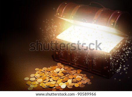 Old wooden treasure chest with strong glow from inside. - stock photo