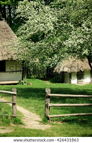 old wooden ukrainian house with clay walls and straw roof in summer garden - stock photo