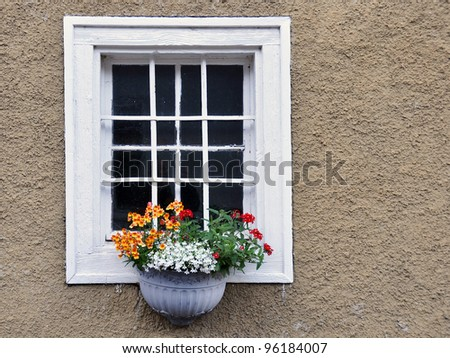 Old wooden window decorated with flowers - stock photo