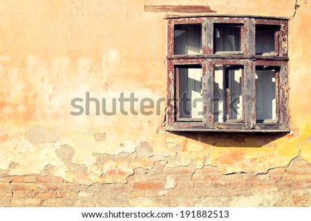 Old wooden window on the yellow brick wall - stock photo