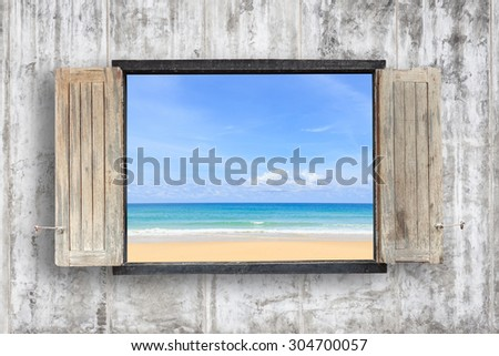 Old wooden windows frame on cement wall and view of tropical sea - stock photo