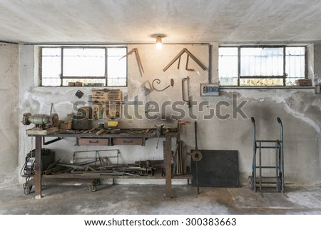 old workbench with old work tools in home garage - stock photo