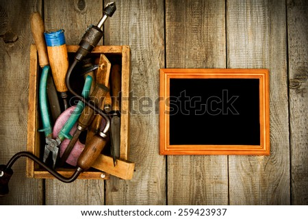Old working tools. Frame with old tools (scissors, pliers, saw and others) in a box on a wooden background. - stock photo