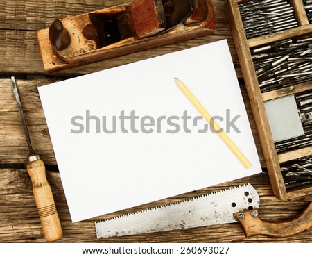 Old working tools. Paper with pencil and the vintage working tools (drills, saw and others) on wooden background. - stock photo