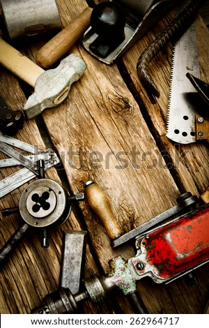 Old working tools. Vintage working tools (drill, saw, ruler and others) on wooden background. - stock photo