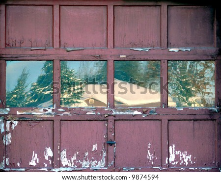 Old workshop door with a winter scene reflecting in the windows - stock photo