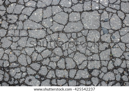 Old worn and cracked asphalt with cracks - stock photo