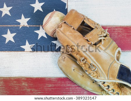Old worn baseball mitt and baseball on faded wooden boards painted red, white and blue with flag pattern.  - stock photo