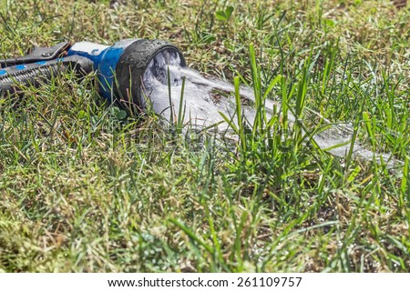 Old worn garden hose spray gun spraying water on green and dry grass, shallow depth of field. Low angle front view. Abandoned sprayer left on a thirsty lawn.   - stock photo