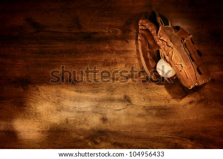 Old worn leather baseball glove and used ball on nostalgic Americana sport wood plank background - stock photo