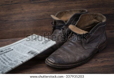 Old worn out brown leather shoes with newspaper over the brown background - stock photo