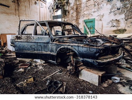 Old wrecked car inside of ruinous building - stock photo