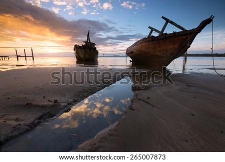 Old wrecked ship at sunrise in Kuala Penyu, Sabah, Borneo, East Malaysia - stock photo
