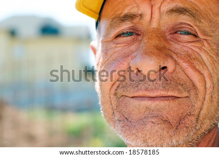 Old wrinkled man with yellow cap against blurry background - stock photo