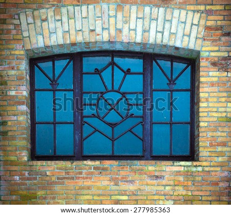 Old wrought window in the wall of brick - stock photo