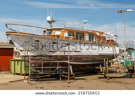 Old yacht undergoing repairs while docked on the quay. - stock photo