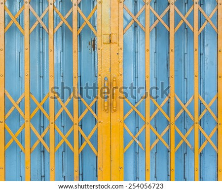 old yellow and blue steel door - stock photo