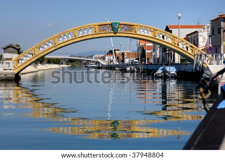 Old yellow bridge across the small channel - stock photo