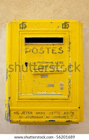 Old yellow French letterbox - stock photo