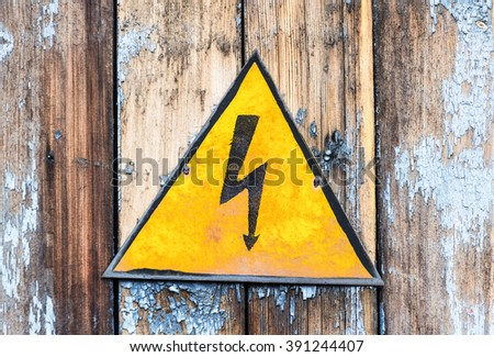 Old yellow high voltage caution sign hanging on the grunge wooden boards - stock photo