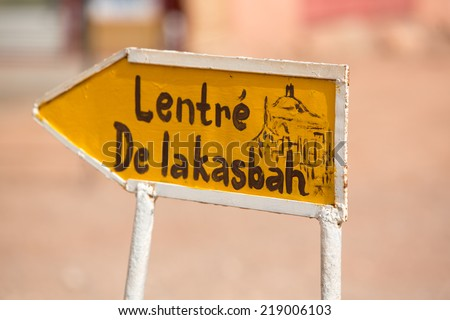 Old yellow Open sign to the fortified city in Ait-ben-Haddou, a fortified city, or ksar, along the former caravan route between the Sahara and Marrakech. Ait Benhaddou is UNESCO World Heritage site - stock photo