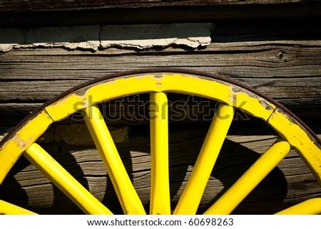 old yellow wood coach wheel - stock photo