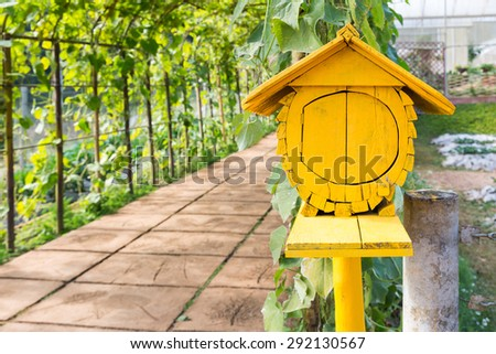 Old yellow wooden bird house in garden vintage style - stock photo