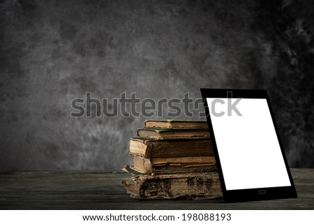Old yellowed books and self-designed tablet computer with blank display  - stock photo