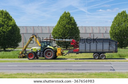 OLDENZAAL, NETHERLANDS - JUNE 15, 2015: Tractor mowing grass along a road - stock photo