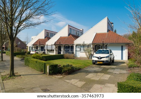 OLDENZAAL, NETHERLANDS - MARCH 23, 2015: Modern row of identical detached houses with front garden and own parking lot - stock photo
