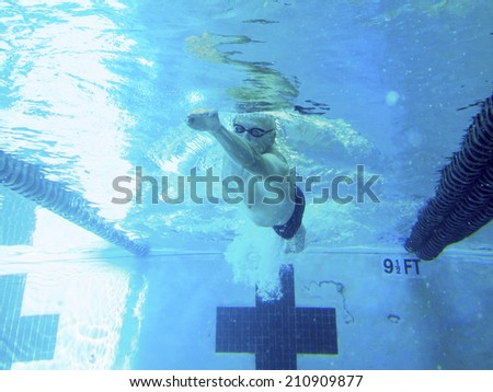 older adult man swimming laps in pool, view from underwater - stock photo