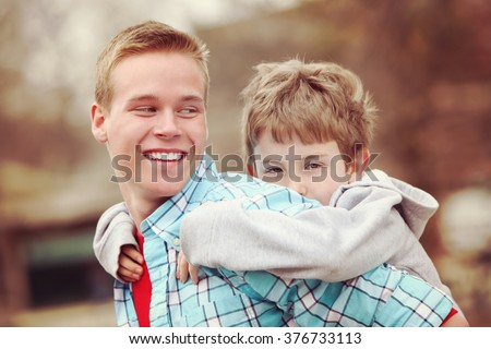 Older brother giving young boy a piggyback ride outdoors smiling  - stock photo