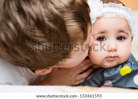 Older brother kissing his newborn baby sister - stock photo