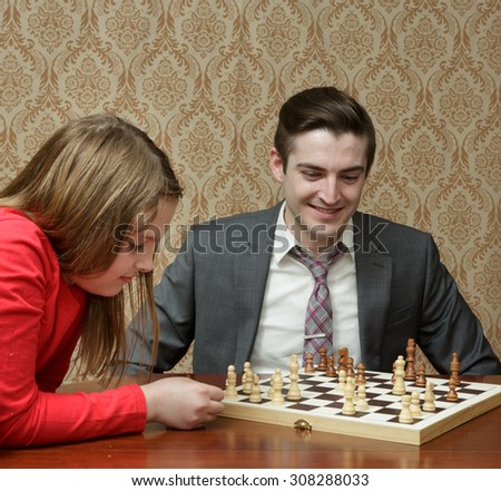 Older brother playing Chess with little sister with no electronics - unpluged and off line - stock photo