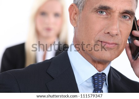 Older businessman using a cellphone - stock photo
