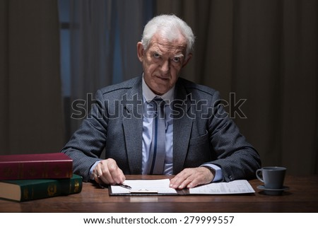 Older busy man working late at night in his cabinet - stock photo