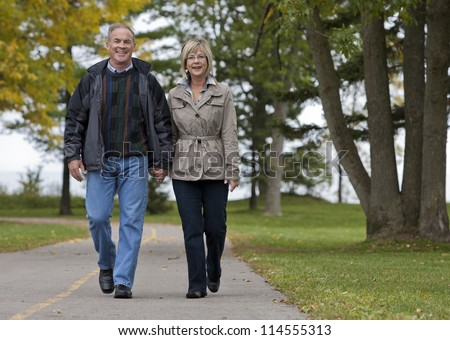 older casual couple walking in the park outdoors - stock photo