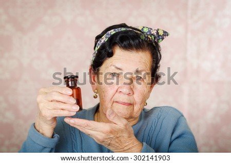 Older cool hispanic woman wearing blue sweater, flower pattern bow on head holding up a small red glass bottle for camera. - stock photo