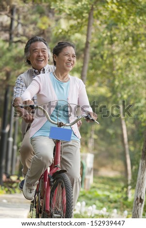 Older couple riding tandem bicycle, Beijing - stock photo